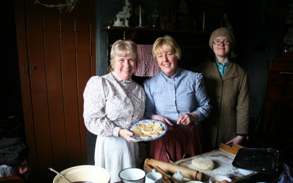 Three pit wives stand in a Pit Cottage at Beamish Museum - Day in the Life of a Pit Wife