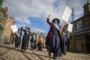 What's on at Beamish in 2020: International Women's Day - A group of women march down The 1900s Town street, demanding the right to vote