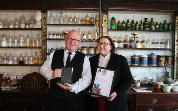 Members of Beamish staff standing in the chemist holding the Beamish Museum Wins Customer Commitment Award